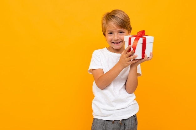 Cute little boy blonde tiene caja de regalo en un amarillo