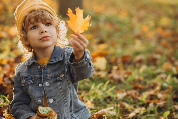 Cute little boy comiendo croissant en el parque