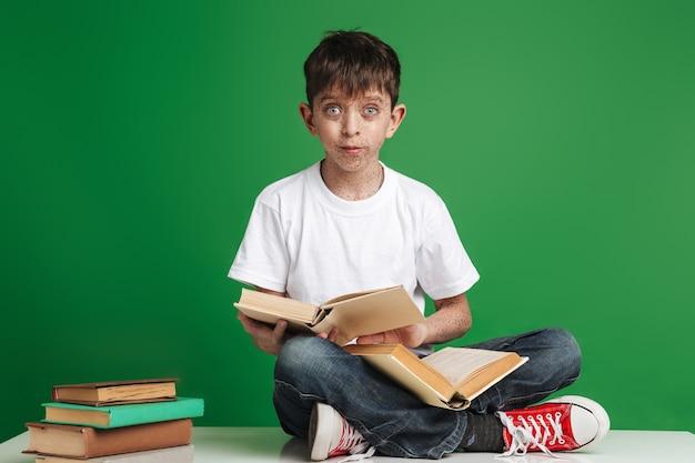 Cute little boy con pecas estudiando, sentado con una pila de libros sobre la pared verde