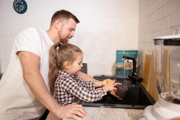 Cute little girl lavando su taza sobre el fregadero con plumero y lavavajillas después de beber té mientras el joven la ayuda