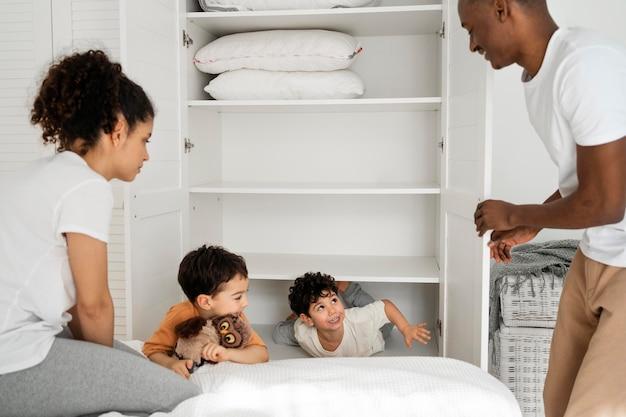 Cutle niños pequeños escondidos en el armario mientras pagan al escondite