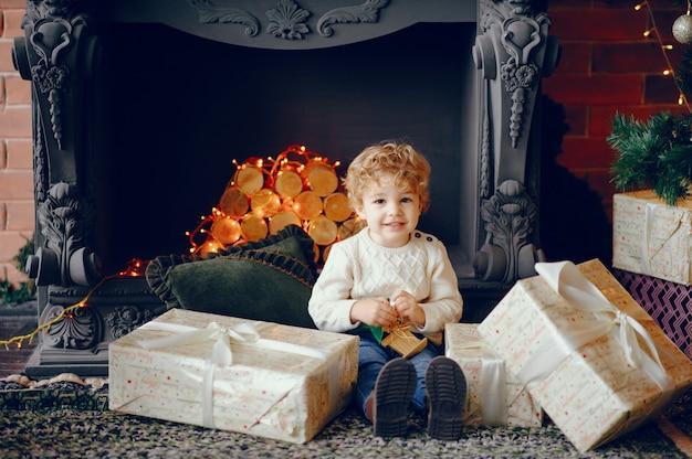 Cutte little boy en casa cerca de decoraciones navideñas