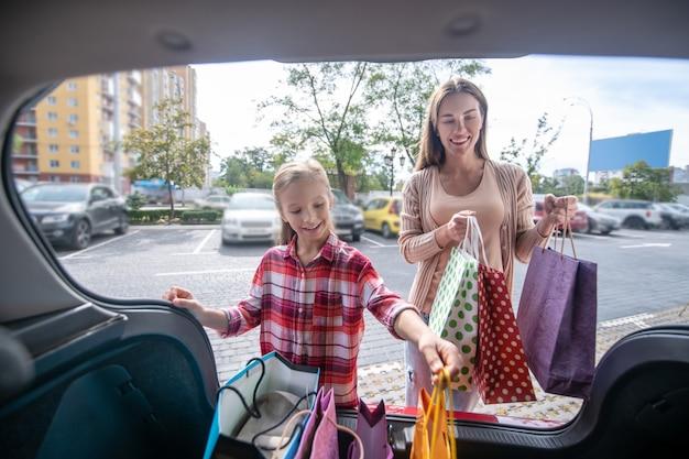 D niña y mujer sonriente sacando bolsas de la compra del maletero del coche