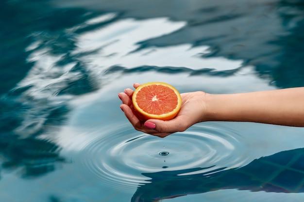 Da a una mujer joven que sostiene un pomelo rojo cerca con agua azul. comida sana