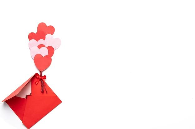 Da de san valentín con corazones rojos y rosas con sobre rojo