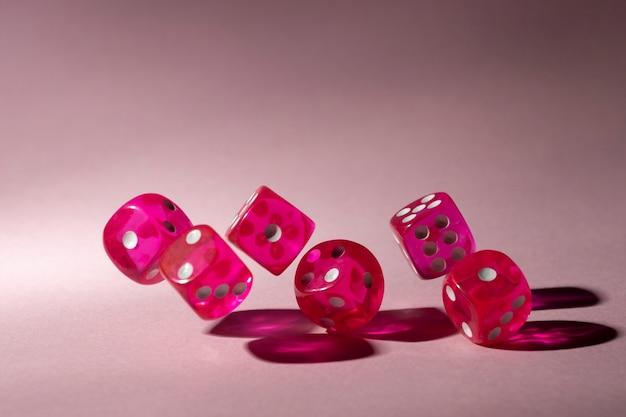 Dados de color rosa sobre fondo rosa