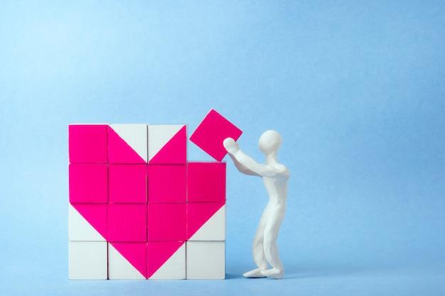Dados corazón. un hombre de plastilina blanca pone el último dado. concepto de medicina, día de san valentín, día de la mujer. concepto de tarjeta de felicitación