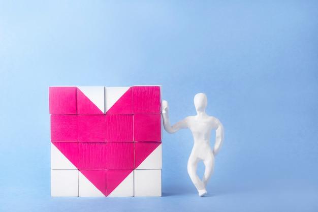 Dados corazón. a su lado, inclinado, se encuentra un hombre de plastilina blanca. concepto de medicina, día de san valentín, día de la mujer. concepto de tarjeta de felicitación