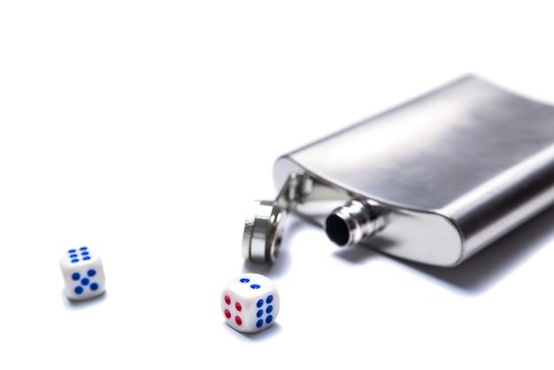 Dados y frasco de metal abierto para alcohol sobre un fondo blanco.