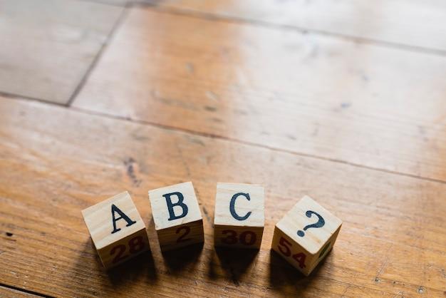 Dados de madera con letras abc e interrogación.