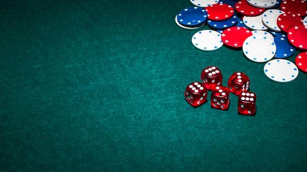Dados rojos brillantes y fichas de casino sobre fondo verde de póquer