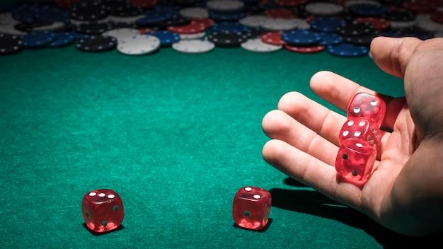 Dados rojos en mano humana en el casino