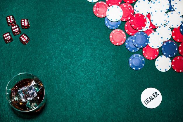 Dados rojos; vaso de whisky; fichas de casino; y distribuidor fichas en la mesa de póquer