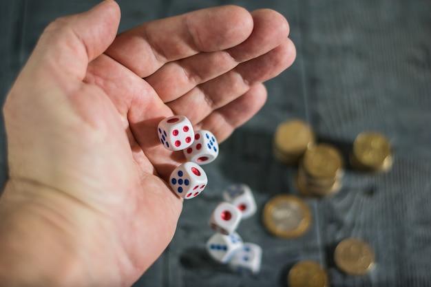Los dados ruedan con los hombres zurdos sobre la mesa con dinero.