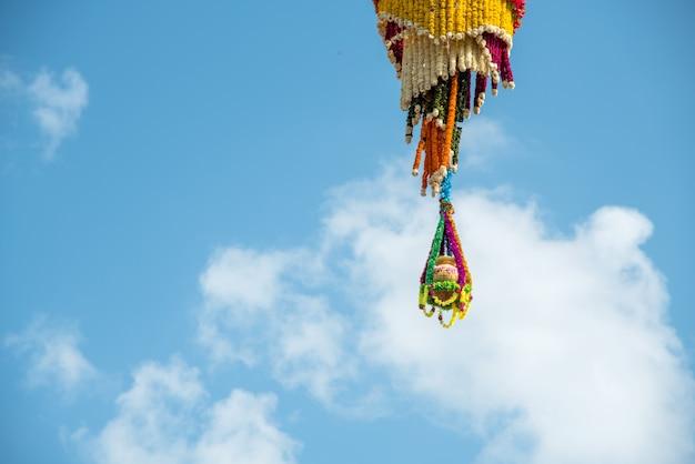 Dahi handi en el festival gokul ashtami con una olla colgante que se llena con cuajada con decoración floral.