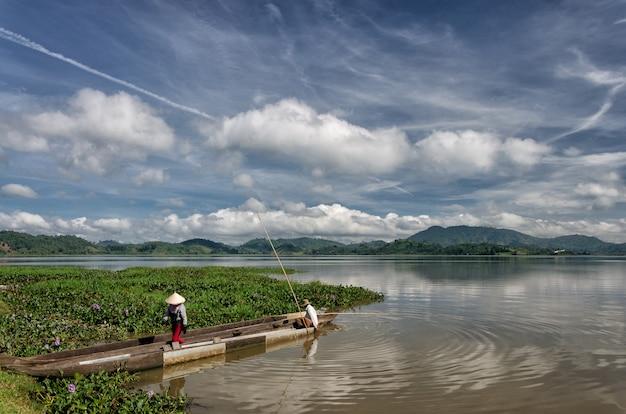 Dak lak - viet nam: grupo de agricultores asiáticos van a trabajar en bote de remos en el lago lak en otoño