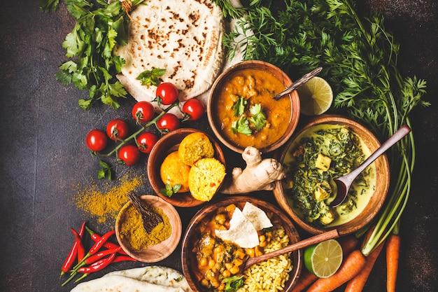 Dal, palak paneer, curry, arroz, chapati, chutney en cuencos de madera en la mesa oscura.