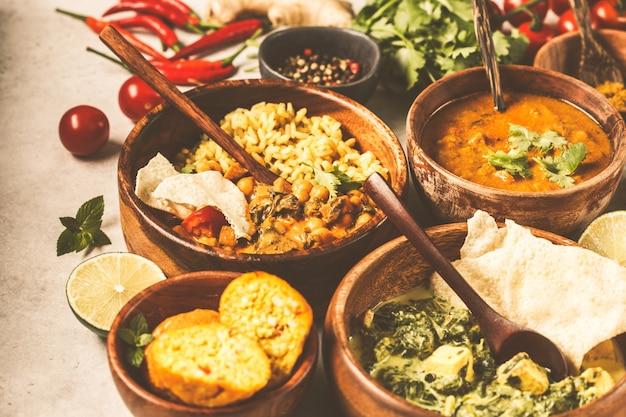Dal, palak paneer, curry, arroz, chapati, chutney en cuencos de madera sobre la mesa blanca.