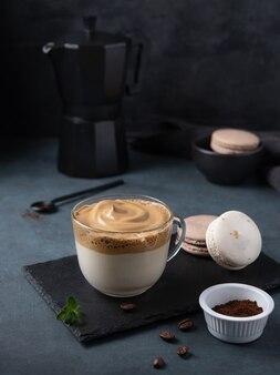 Dalgona café en taza con macarrones sobre fondo amarillo