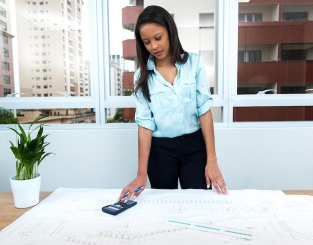 Dama afroamericana con bolígrafo y calculadora cerca del plan en la mesa