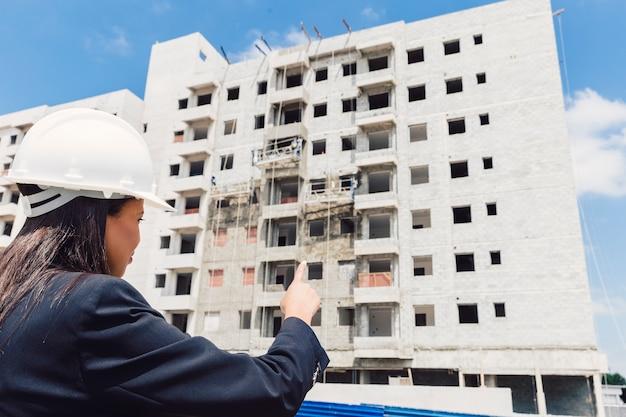 Dama afroamericana en casco de seguridad apuntando al edificio en construcción