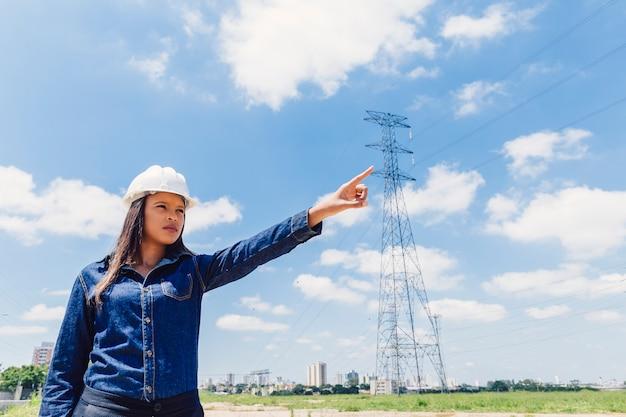 Dama afroamericana en casco de seguridad apuntando cerca de línea de alto voltaje