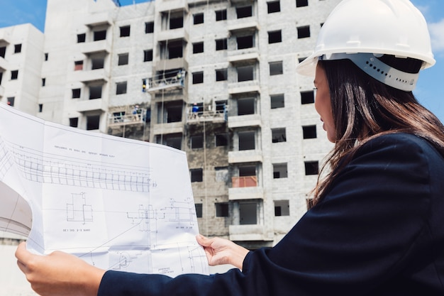 Dama afroamericana en casco de seguridad con plan de papel cerca del edificio en construcción