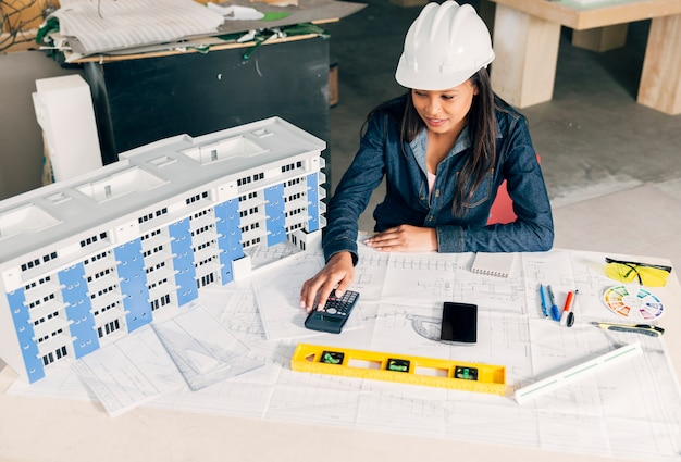 Dama afroamericana en casco de seguridad sentada cerca del modelo de edificio