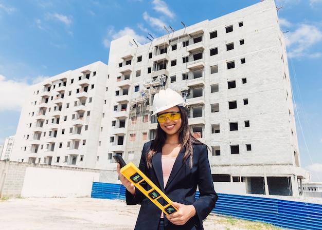 Dama afroamericana en casco de seguridad con teléfono inteligente y nivel de edificio cerca del edificio en construcción