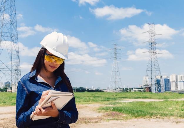 Dama afroamericana en casco de seguridad tomando notas cerca de línea de alto voltaje