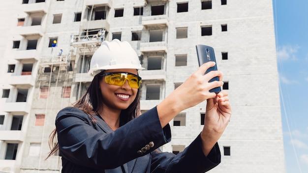 Dama afroamericana en casco de seguridad tomando selfie cerca de edificio en construcción
