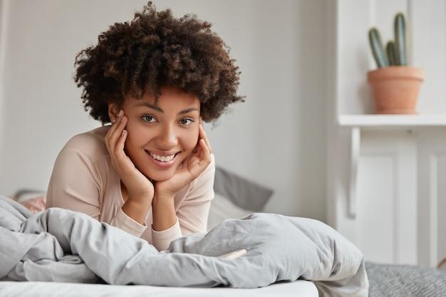 La dama afroamericana perezosa mantiene ambas manos en las mejillas, usa ropa de dormir, disfruta del tiempo libre en la cama, tiene recreación en el dormitorio, amplia sonrisa. el ama de casa descansa de la rutina de la casa. concepto de mañana