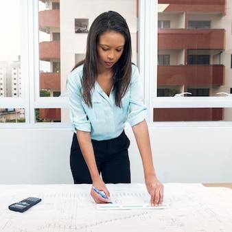 Dama afroamericana con pluma y regla cerca del plan en la mesa