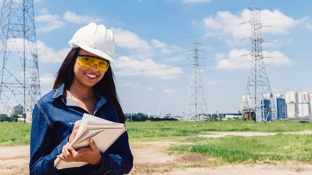 Dama afroamericana sonriente en casco de seguridad tomando notas cerca de línea de alto voltaje
