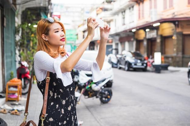 Dama atractiva disparando en el teléfono inteligente