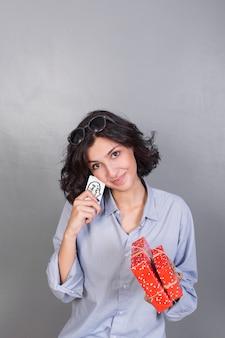 Dama atractiva con regalos y tarjeta.