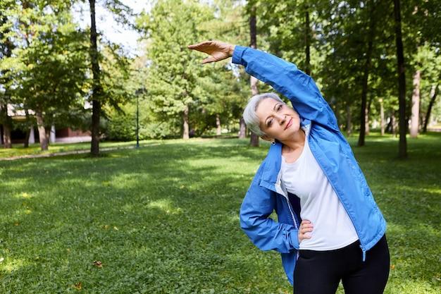 Dama caucásica senior de cabello gris activa sosteniendo una mano en la cintura y levantando el brazo mientras hace curvas laterales en el parque, calentando el cuerpo antes del entrenamiento cardiovascular, teniendo una expresión facial feliz y alegre