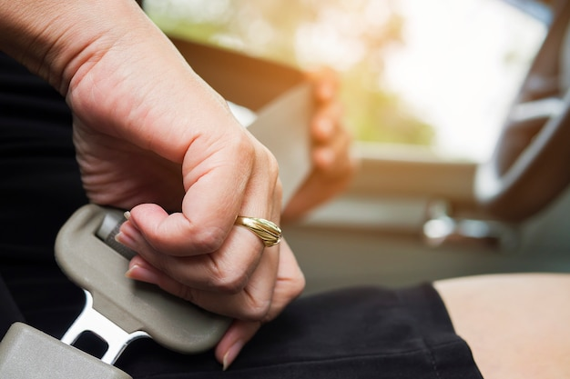 Dama colocando el cinturón de seguridad del automóvil antes de conducir, de cerca en la hebilla del cinturón, concepto de manejo seguro