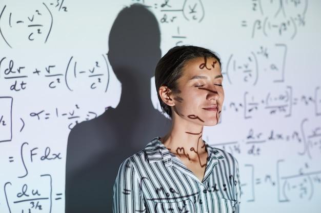 Dama contra pantalla de proyección con fórmulas matemáticas