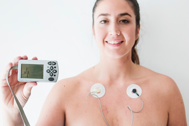 Dama con electrodos sosteniendo monitor con cardiograma