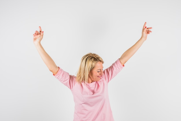 Dama feliz envejecida en blusa rosa con las manos levantadas