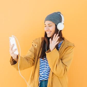 Dama feliz saludo durante una llamada de video con un teléfono inteligente