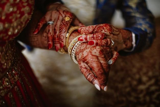 Dama de honor ayuda a la novia india a ponerse joyas en la mano
