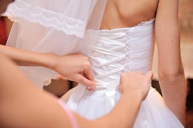 Dama de honor está ayudando a la novia a vestirse