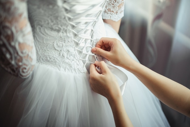 Dama de honor hace nudo de lazo en la parte posterior de las novias vestido de novia