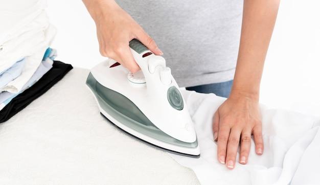 Dama irreconocible planchando ropa