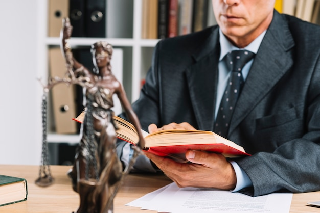 Dama de la justicia frente a abogado leyendo el libro de leyes en la sala del tribunal