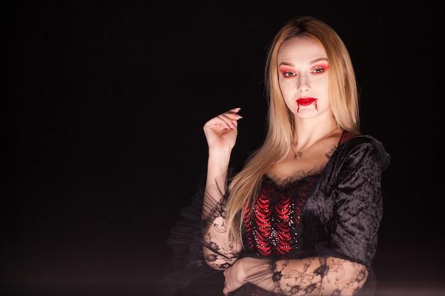 Dama de la muerte con sangre que gotea de los labios sobre fondo negro. disfraz de halloween.