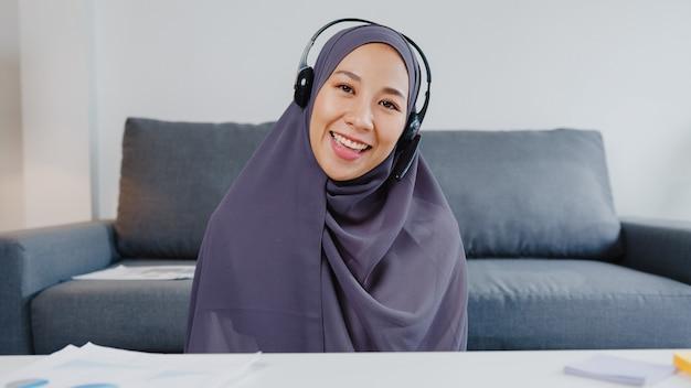 La dama musulmana de asia usa auriculares usando una computadora portátil y hable con sus colegas sobre el plan en una reunión de videoconferencia mientras trabaja de forma remota desde su casa en la sala de estar