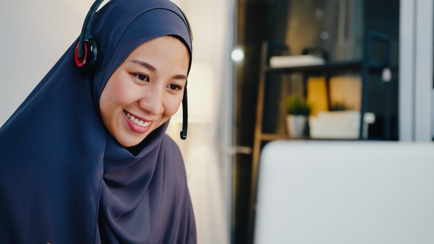 Dama musulmana usa audífonos ver seminario web escuchar curso en línea comunicarse por videoconferencia en la oficina en casa de noche.